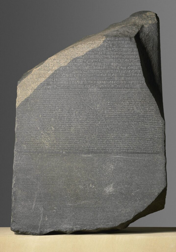 Rosetta Stone Part of grey and pink granodiorite stela bearing priestly decree concerning Ptolemy V in three blocks of text: Hieroglyphic(14 lines), Demotic(32 lines) and Greek(53 lines).